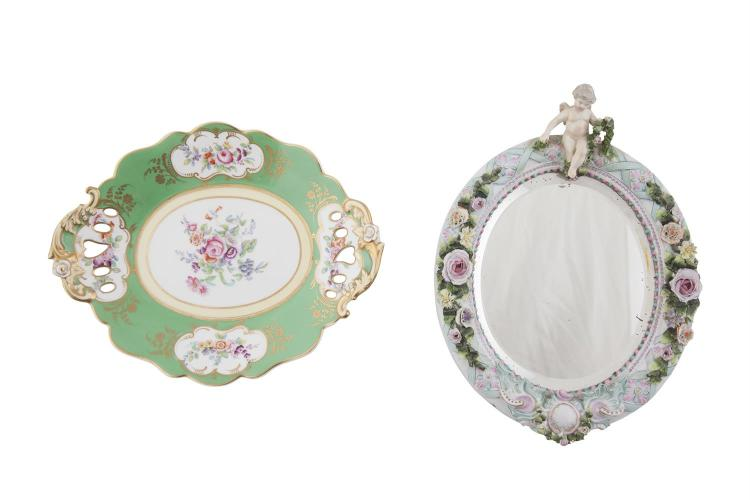 A MEISSEN POLYCHROME PORCELAIN OVAL TABLE MIRROR, the frame decorated with encrusted flowers and surmounted with a putto. 30 x 22cm; together with a Victorian apple green and gilt oval fruit dish. (2)