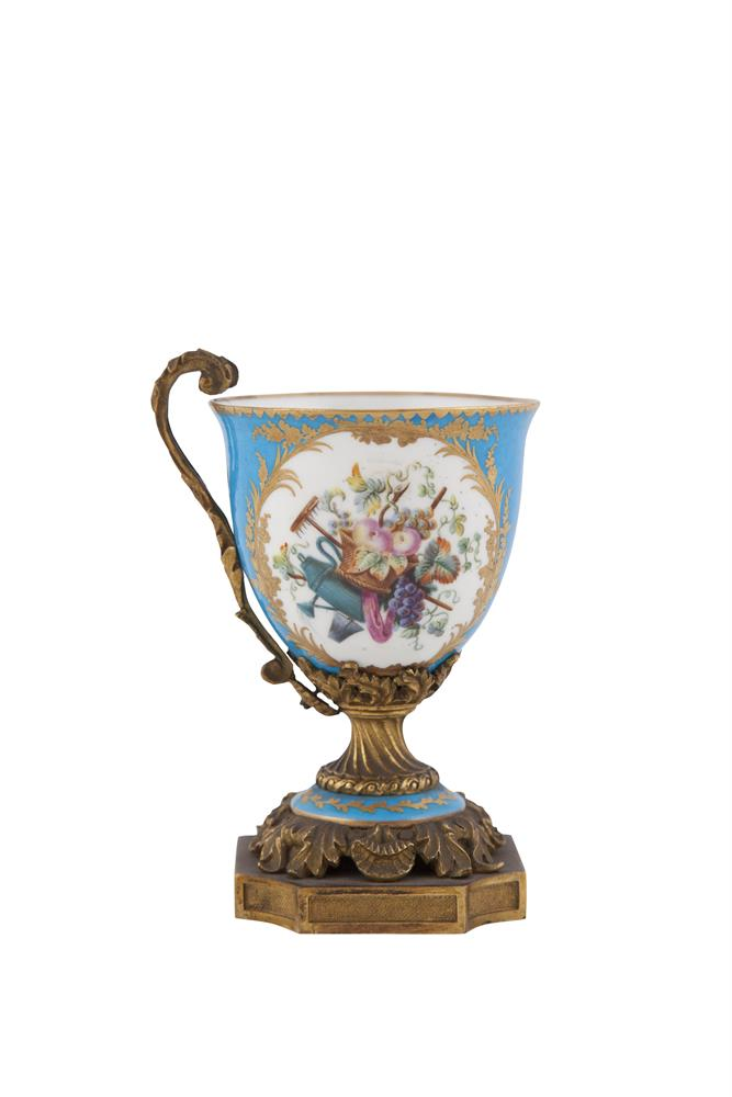 A SEVRES PORCELAIN AND ORMOLU CHOCOLATE CUP, decorated with panels of love-birds and gardening motifs, the mounts cast and engraved with foliate scrollwork and raised on platform base. 14cm high