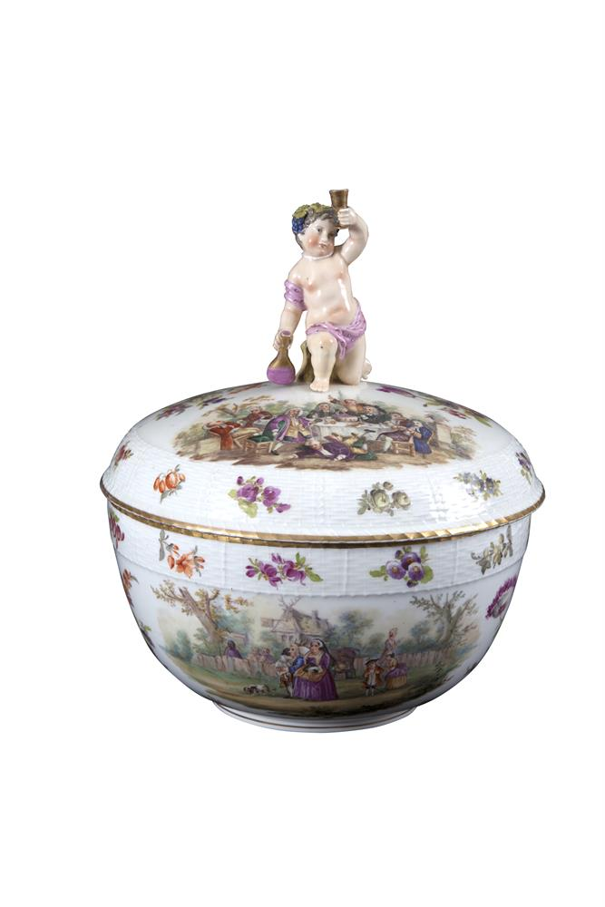 A LARGE BERLIN PORCELAIN CIRCULAR BOWL AND COVER, 19th century, surmounted with a figure of a cherub raising a goblet and decorated with numerous ceremonies and scattered floral sprays, with basket weave borders, repeated again to the base, cancelled