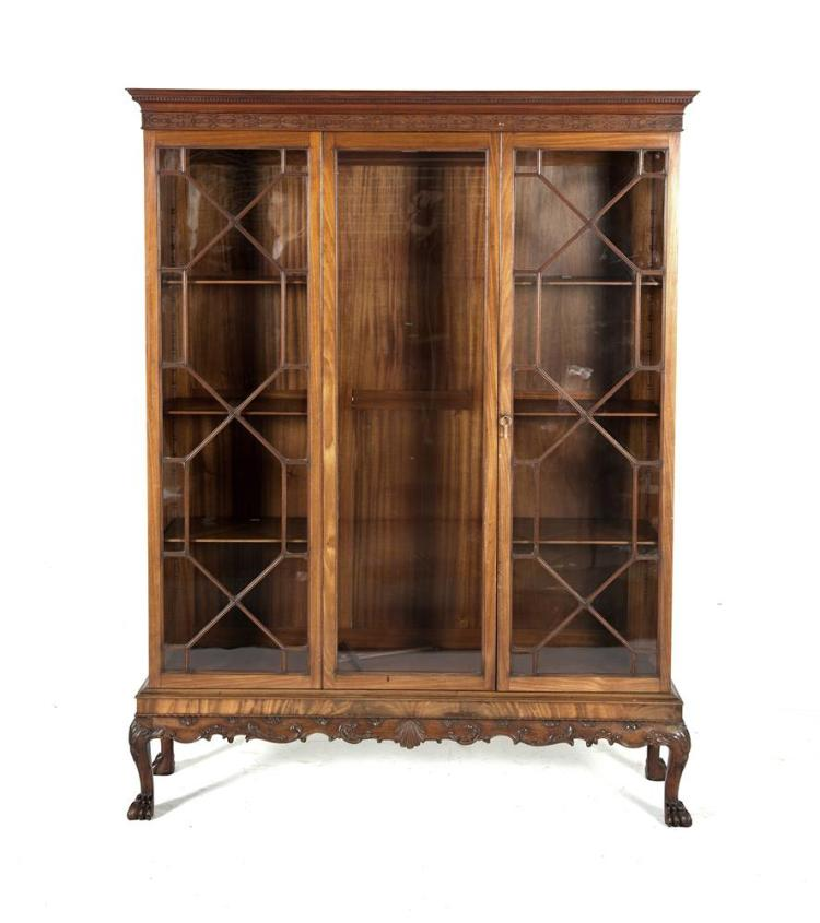 A GEORGIAN STYLE MAHOGANY TRIPLE DOOR DISPLAY CABINET, in the manner of James Hicks with dentil cornice and blind fret frieze above twin astragal glazed panel doors flanking a glazed sliding panel and raised on a carved base with shell and scroll dec