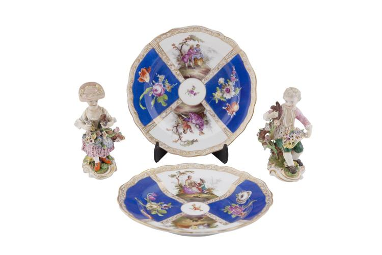 A PAIR OF MEISSEN POLYCHROME PORCELAIN FIGURES OF A BOY AND GIRL, seated with flowers, on a naturalistic oval shaped base. 12.5cm high; together with a pair of Helena Wolfsohn plates. (4)