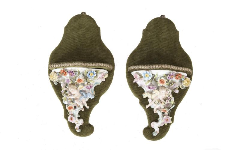 A PAIR OF SITZENDORF POLYCHROME PORCELAIN WALL BRACKETS, with putti and floral decoration in high relief, mounted on green plush base. 44cm high overall