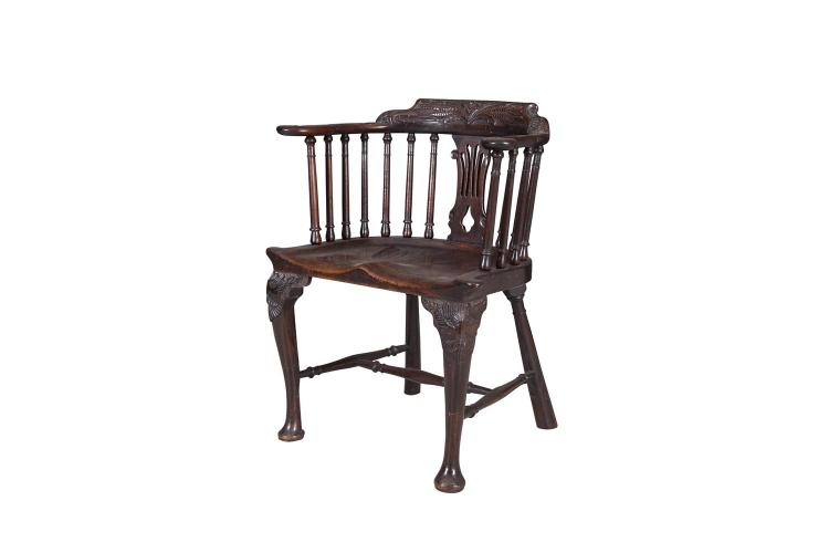 A CARVED ELM TUB CHAIR, the curved back with wheat sheaf crest rail above solid seat on cabriole legs and pad feet