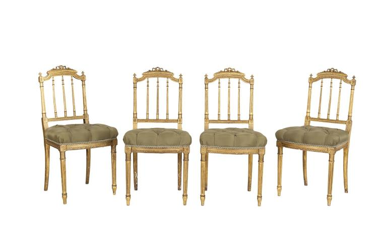 A SET OF FOUR FRENCH GILTWOOD AND UPHOLSTERED SALON CHAIRS, c.1900, each with a ribbon tied top rail above turned and fluted column supports, with olive button upholstered seat and fluted forelegs