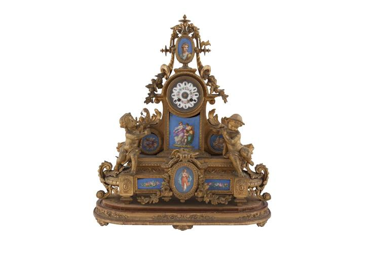 ***PLEASE NOTE ESTIMATE SHOULD READ € 500 - 700 IN PRINTED CATALOGUE***A GILT SPELTER CASED MANTLE CLOCK, French late 19th century, the cylindrical dial surmounted by a portrait medallion on an oval base with musicians and inset with further porcela