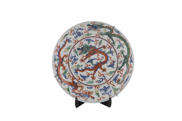 A CHINESE DOUCAI ENAMEL DRAGON DISH, 19th century, of circular form, painted and enamelled with dragons contesting the flaming pearl, in green, blue and iron red, the underside decorated with auspicious emblem and six character Ming marks. 24.5cm dia