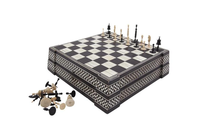 A LATE 18TH / EARLY 19TH CENTURY 'CAPTAIN COOK STYLE' IVORY CHESS SET, one side stained black, the other side left natural. The King 8cm tall; together with a 19th Century ebony and ivory inlaid hinge-top chess box, of square tapering form. 35 x 35cm