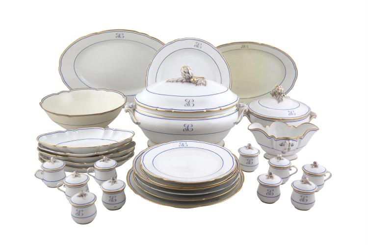 A LATE 19TH / EARLY 20TH CENTURY DINNER SERVICE, the white ground with blue and gilt decoration, crested, comprising: 43 dinner plates, 17 soup plates of various sizes, 2 large oval serving plates of various sizes, 1 large bowl on foot, 1 large oval