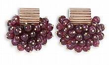 A PAIR OF GARNET EARCLIPS, CIRCA 1940Each earclip designed as a cluster of grapes, set with ruby cabochons with polished spherical accents, suspended from a polished reeded surmount, mounted in gold, length 2.1cm