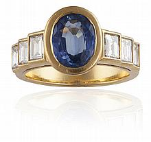 A SAPPHIRE AND DIAMOND RINGThe oval-shaped sapphire, weighing approximately 1.90cts, between tapering shoulders of baguette-cut diamonds, mounted in 18K gold, diamonds approximately 1.40cts total, ring size M