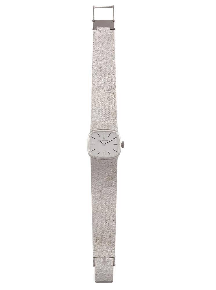 A LADY'S 18K GOLD MANUAL WIND BRACELET WATCH, BY CERTINA, CIRCA 1960The cushion-shaped silvered signed dial, with black baton numerals, on integral textured bracelet strap, mounted in 18K gold, serial #0426035, Swiss assay mark, length 18.5cm, appro