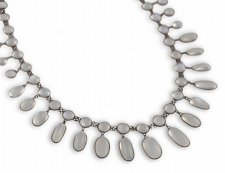 AN EARLY 20TH CENTURY MOONSTONE FRINGE NECKLACEComposed of a series of circular and oval cabochon moonstones suspended from similarly-cut moonstones, to a trace-link chain, mounted in 14K gold, length 43cm