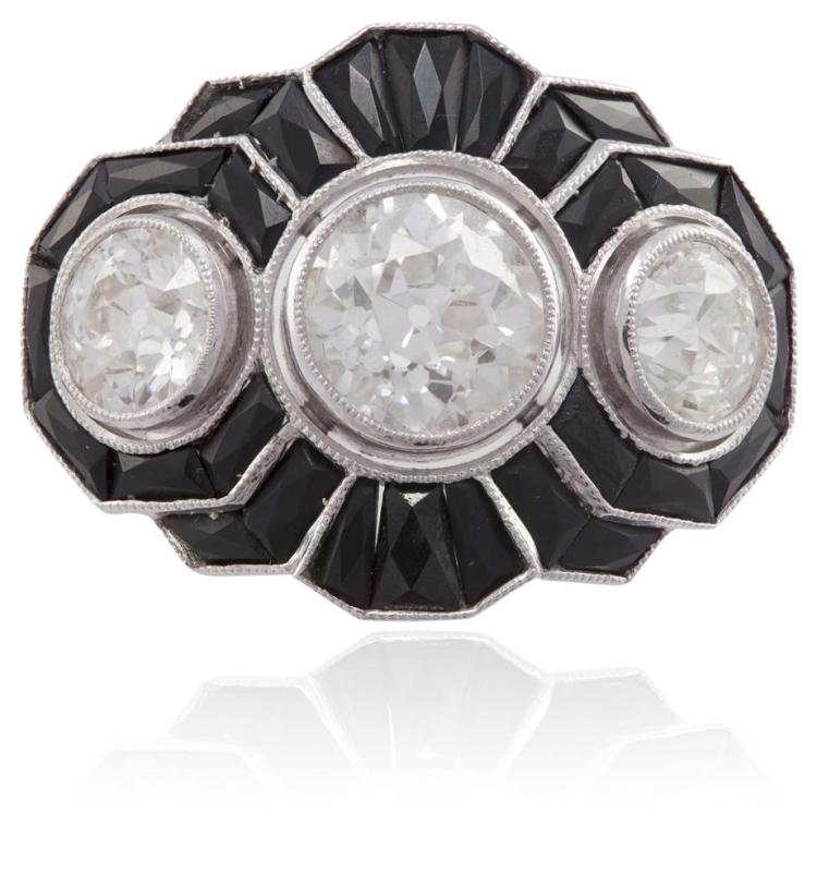 AN ART DECO DIAMOND AND ONYX RINGOf stylised scalloped form, set centrally with an old round brilliant-cut diamond, weighing approximately 1.30cts, between two similarly-cut diamonds, surrounded by a frame of calibré-cut onyx, remaining diamonds app