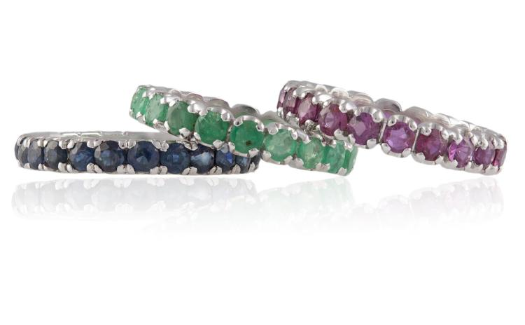 A SET OF THREE FULL HOOP ETERNITY RINGSEach set with circular-cut emeralds, rubies or sapphires throughout, within four-claw setting, mounted in 18K gold, ring size N (2), O