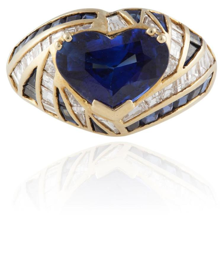 A SAPPHIRE AND DIAMOND RINGThe heart-shaped sapphire, weighing approximately 2.70cts, within a surround of baguette-cut diamonds and calibré-cut sapphires, mounted in 18K gold, Italian assay mark, ring size L* Please note that the heart-shaped sap