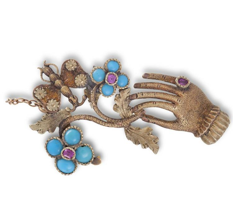 A GEORGIAN SENTIMENTAL FORGET-ME-NOT PENDANT/BROOCH, CIRCA 1825The gloved hand set with a round-shaped ruby, holding delicately the tip of a flower stalk, set with cabochon turquoises and round-shaped rubies, the reverse revealing a small glazed c