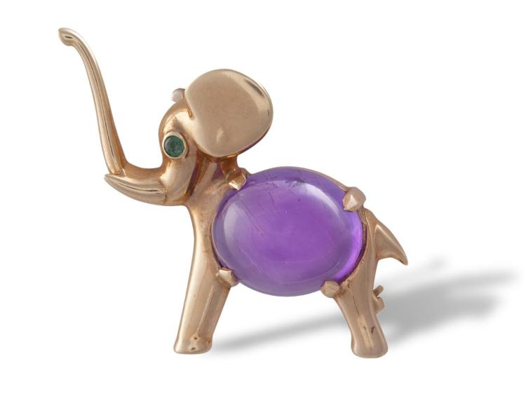 AN AMETHYST AND EMERALD NOVELTY BROOCHModelled as a small elephant, the body set with an oval-shaped cabochon amethyst, the eye with a circular-cut emerald, mounted in 9K gold, French assay mark, width 3.2cm