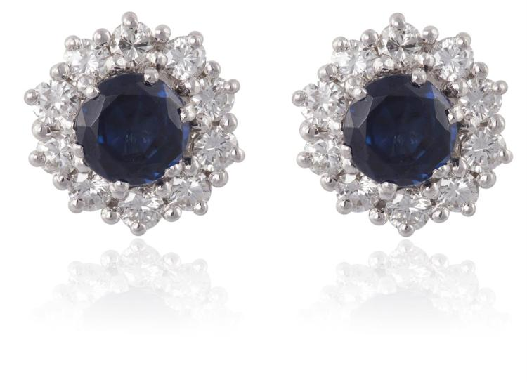 A PAIR OF SAPPHIRE AND DIAMOND CLUSTER EARSTUDSEach set centrally with a round-shaped sapphire, framed by a surround of round brilliant-cut diamonds, mounted in 18K gold, diamonds approximately 0.30ct total, length 9mm