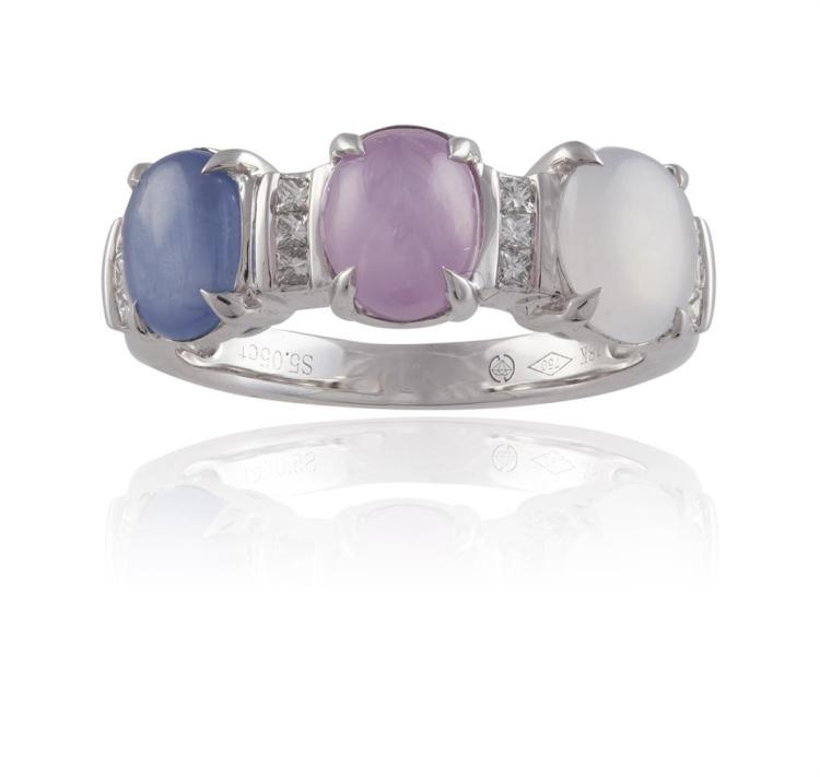 A STAR SAPPHIRE THREE-STONE RINGSet with a trio of colourless, pink and blue oval-shaped cabochon star sapphires, each between round brilliant-cut diamond accents, mounted in 18K gold, ring size M