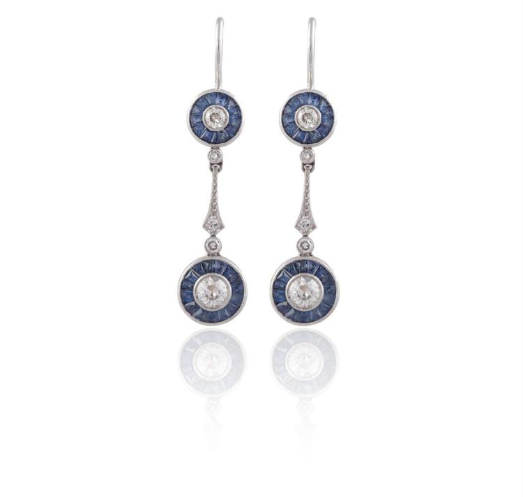 A PAIR OF EARLY 20TH CENTURY DIAMOND AND SAPPHIRE PENDENT EARRINGSEach old brilliant-cut diamond within a calibré-cut sapphire surround, suspended from a single-cut diamond line, to a similarly-cut sapphire and diamond surmount, mounted in platinum,