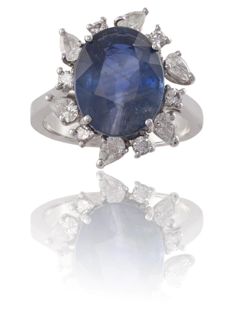 A SAPPHIRE AND DIAMOND CLUSTER RINGThe oval-shaped sapphire, weighing 8.19cts, within a surround of pear and round brilliant-cut diamonds, mounted in 18K gold, diamonds approximately 0.60ct total, Italian assay mark, ring size NAccompanied by a rep