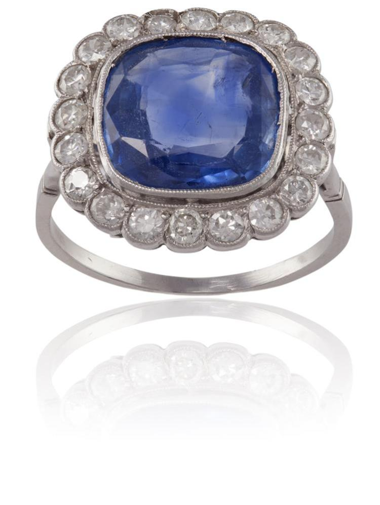 A SAPPHIRE AND DIAMOND CLUSTER RINGThe cushion-shaped sapphire, weighing approximately 4.70cts, within a scalloped surround of round brilliant-cut diamonds, within millegrain setting, mounted in platinum, diamonds approximately 0.60ct total, French