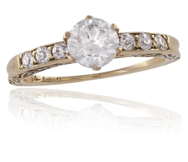 A DIAMOND SINGLE-STONE RINGThe round brilliant-cut diamond, between old brilliant-cut diamond shoulders, with foliate engraved sides, mounted in 14K gold, diamonds approximately 0.80ct total, ring size J
