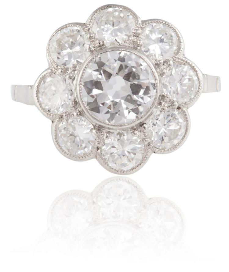 A DIAMOND CLUSTER RINGThe round brilliant-cut diamond, weighing approximately 0.70ct, within a similarly-cut diamond surround, remaining diamonds approximately 1.20cts total, ring size J½