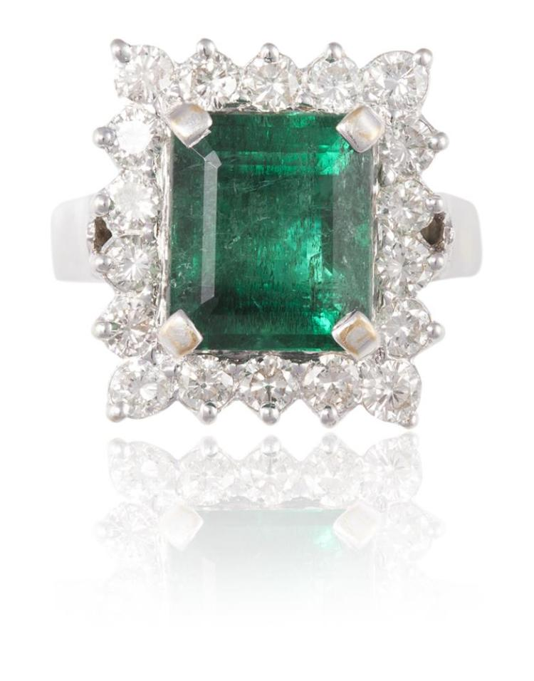 AN EMERALD AND DIAMOND CLUSTER RINGThe rectangular step-cut emerald, weighing 5.35cts, within a border of round brilliant-cut diamonds, mounted in 14K gold, diamonds 1.30cts total, Ring size K½