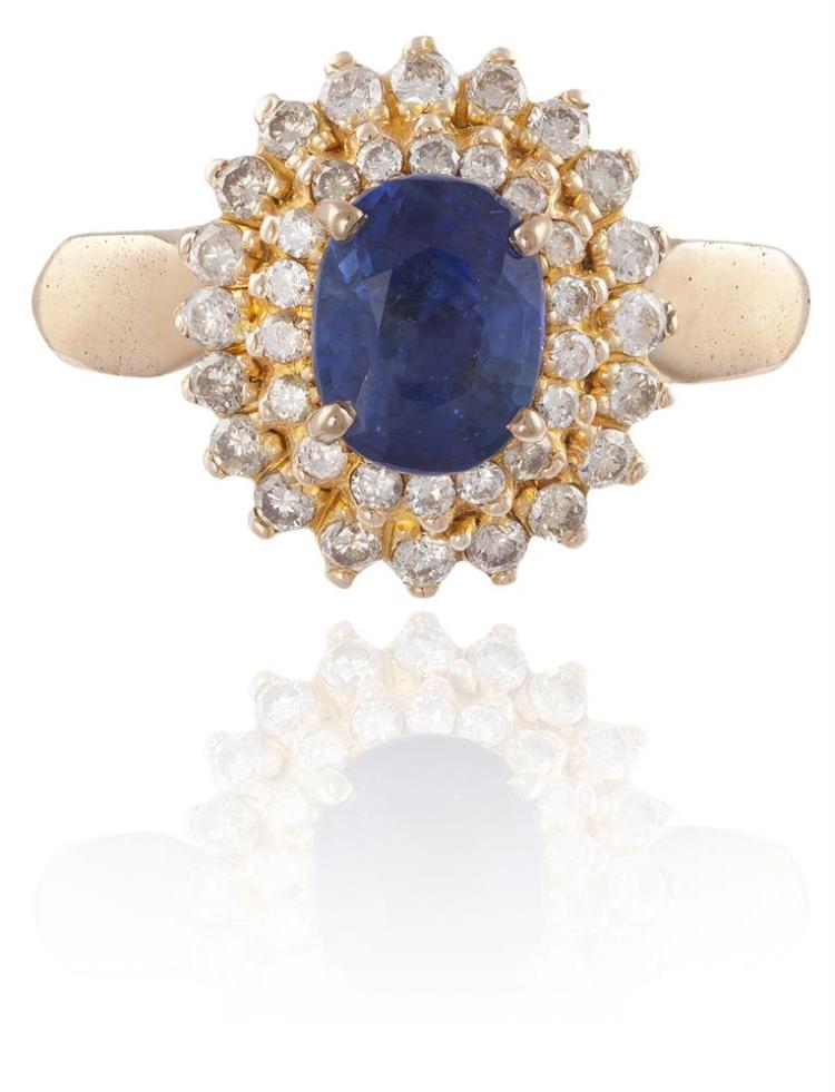 A SAPPHIRE AND DIAMOND CLUSTER RINGThe oval-shaped sapphire, in a four-claw setting, within a brilliant-cut diamond surround, mounted in 18K gold, diamonds approximately 0.20ct total, ring size O½