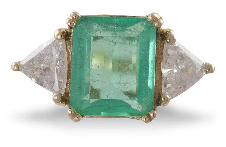 AN EMERALD AND DIAMOND RINGThe rectangular step-cut emerald, weighing approximately 2.90cts, within a double four-claw setting, between two trillion-cut diamonds, mounted in 18K gold, diamonds approximately 0.80ct total, ring size L¾