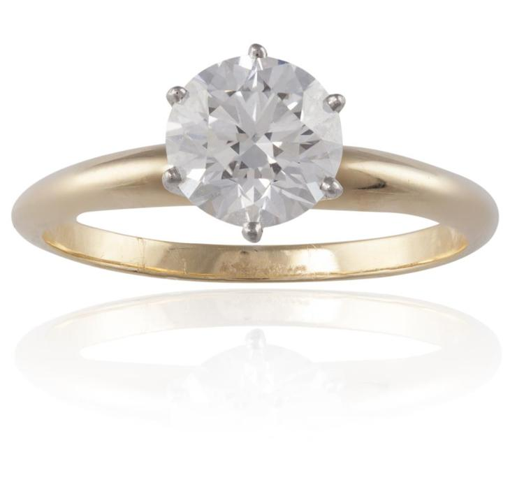 A DIAMOND SINGLE-STONE RING, BY TIFFANY & CO.The round brilliant-cut diamond, weighing approximately 1.10cts, within a six-claw setting, to a plain hoop, mounted in 18K gold, ring size L