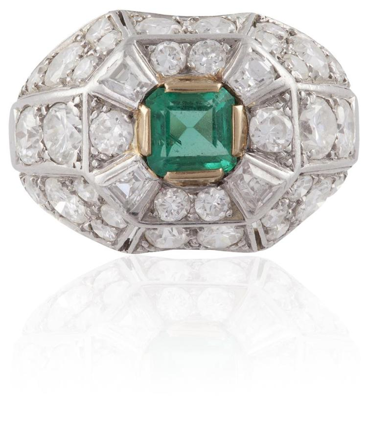 AN EMERALD AND DIAMOND RINGOf bombé design, centrally-set with a step-cut emerald, within a surround of round brilliant and tapered baguette-cut diamonds, diamonds approximately 1.80cts total, ring size P