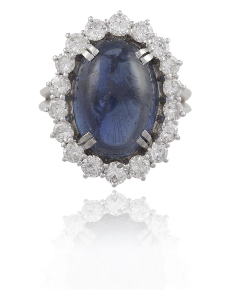 A SAPPHIRE AND DIAMOND CLUSTER RINGThe oval cabochon sapphire, within a surround of round brilliant-cut diamonds, mounted in 18K gold and platinum, diamonds approximately 1.40cts total, ring size M¾