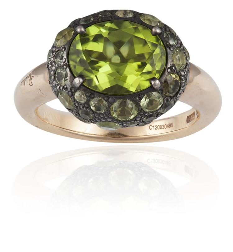 A PERIDOT TABOU DRESS RING, BY POMELLATOThe oval mixed-cut peridot, within a circular-cut peridot surround, mounted in 18K gold and 925 silver, signed Pomellato, numbered C120030485, Italian assay marks, ring size L