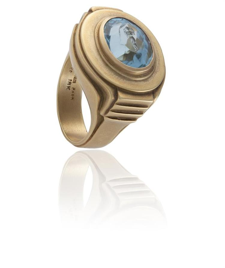 AN BLUE TOPAZ INTAGLIO RING BY BARRY KIESELSTEIN-CORD, 1986The collet-set oval topaz intaglio engraved with a female figure, within a polished mount of asymmetrical tapered design, mounted in 18K gold, signed Kieselstein Cord, 1986, ring size P½Ki