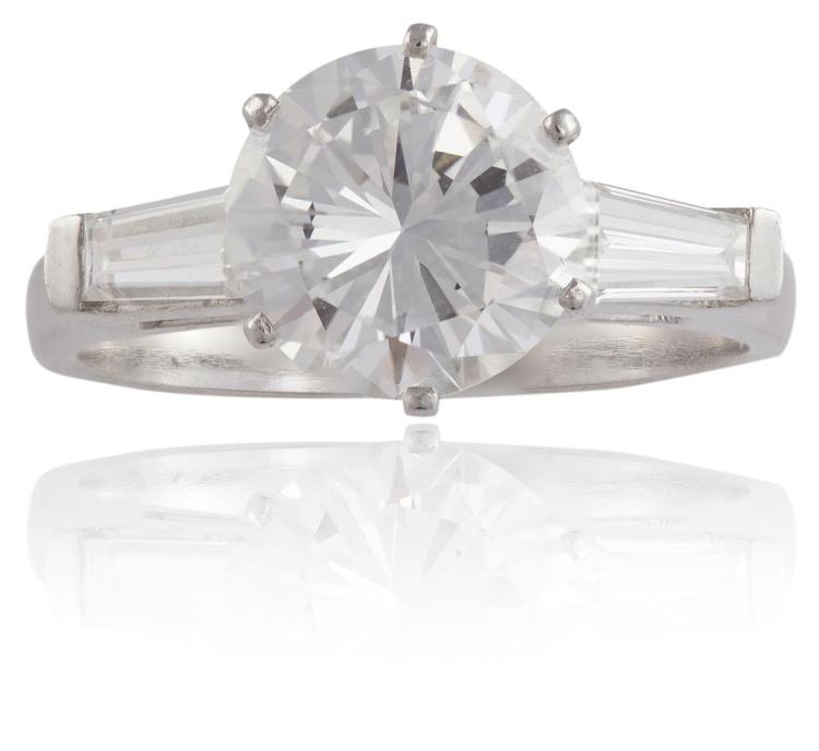 A DIAMOND SINGLE-STONE RINGSet with an round brilliant-cut diamond, weighing 2.07cts, between tapered baguette-cut diamond shoulders, mounted in platinum, ring size KAccompanied by a GIA certificate, stating that the diamond weighing 2.07cts is F c