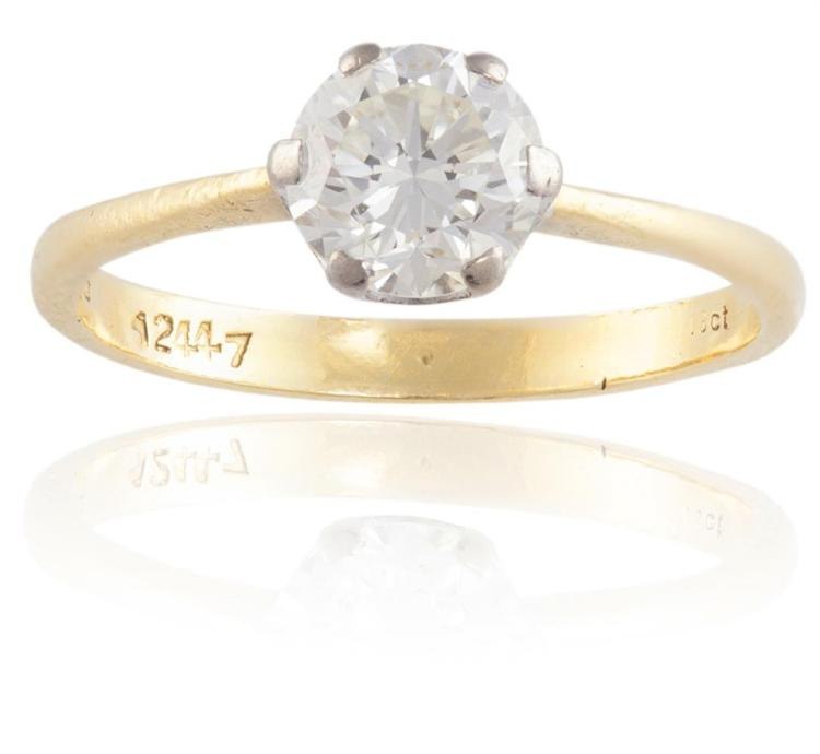 A DIAMOND SINGLE-STONE RINGThe round brilliant-cut diamond, weighing approximately 1.10cts, set within a six-claw setting, to a plain hoop, mounted in 18K gold, ring size N¾