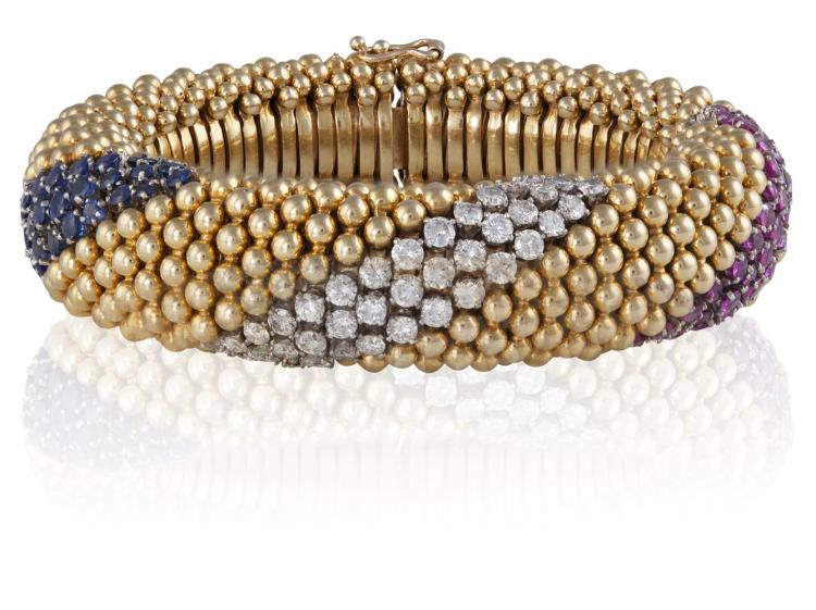 A RUBY, DIAMOND AND SAPPHIRE BRACELET, CIRCA 1965Of flexible tubular design, composed of a clustered band of polished spherical beads, striated with trio-lines of brilliant-cut rubies, diamonds and sapphires, to a concealed clasp, mounted in 14K gol
