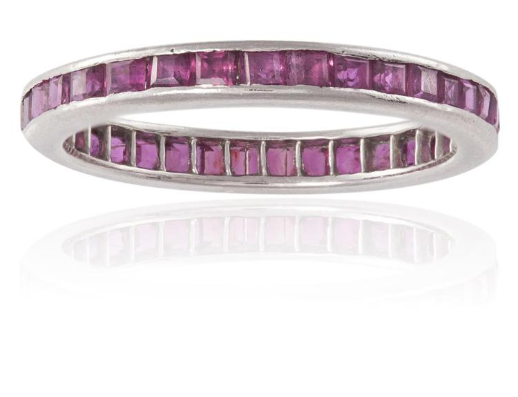 A RUBY FULL HOOP ETERNITY RING, BY TIFFANY & CO.Channel-set with a line of calibré-cut rubies, mounted in platinum, signed Tiffany & Co., ring size L