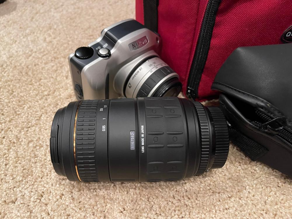 LOT OF CAMERAS AND CASES. NIKON PRONEAS WITH QUANTARAY 70-300 MM LENS. CANON ELPH2 CAMERA WITH SPEED LIGHT 200 E