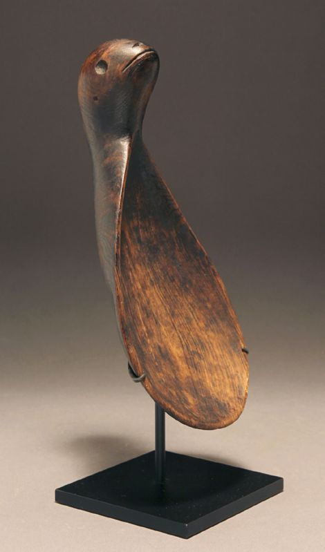 AN ELEGANTLY CARVED NATIVE AMERICAN ESKIMO WOOD LADLE DEPICTING A SEAL
