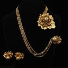 Miriam Haskell gold tone floral brooch, multi strand chain, clip and earrings.