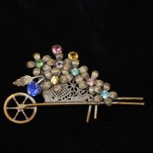 Metal filigree wheel barrow cart figural pin / brooch with flowers and pastel jewel rhinestones.