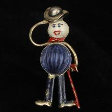 Jewel bellied figural hat tipping man with a cane novelty pin / brooch; patriotic red, white and blue enamel and blue figured glass.