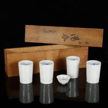 Japanese porcelain set of sake drinking cups in two wood boxes with blue and white interior decoration, 9 cups and one bowl.