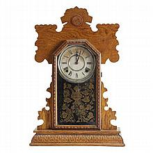 Ingraham Victorian gingerbread mantel clock; oak case with reverse decoration on glass door.