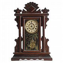 Victorian gingerbread mantel clock; mahogany case with reverse decoration on glass door.