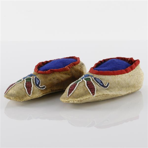 Santee Sioux leather child's moccasin slippers with trade cloth trim and beaded pepper design.