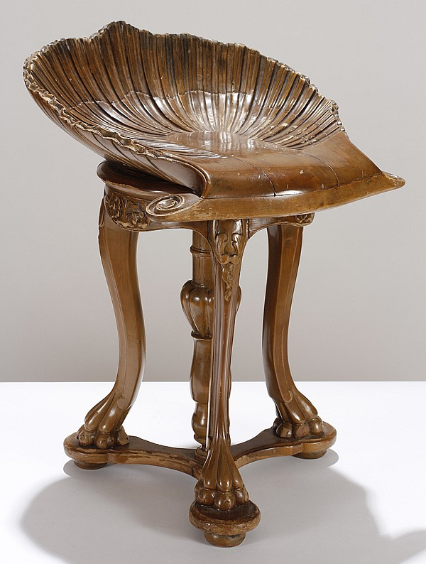 Carved walnut piano stool; seashell swivel seat, paw feet.